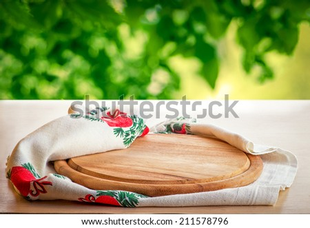 Board for pizza on the kitchen table in the garden - stock photo