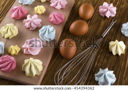 Board of homemade pastel colored meringue cookies. - stock photo
