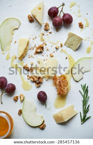 board with cheese, honey, fruits and nuts - stock photo