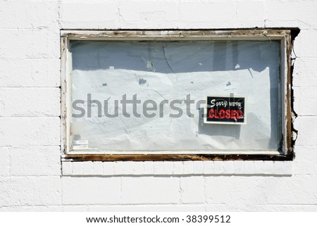 "boarded up white window of bankrupt business with ""Sorry we're closed"" sign"