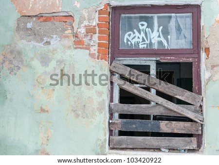 Boarded-up window in an abandoned old building. - stock photo