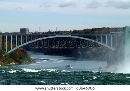 Boarder crossing Canada - USA showing the Rainbow Bridge and tourist boat on the international divide in the middle of the Niagara River. In the foreground is the brink of Canada's Horseshoe  Falls. - stock photo