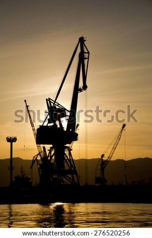 boarding ship, Silhouettes of cranes which loaded cargo on board - stock photo