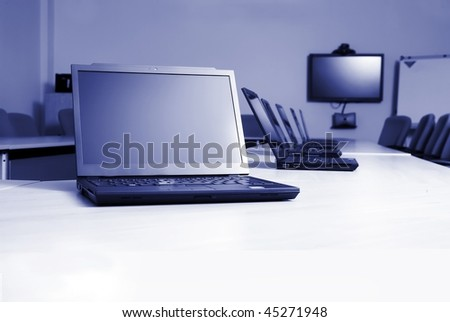 Boardroom with laptops and video conferencing equipment - stock photo