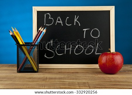 boards for writing, pencils and an apple on a blue background - stock photo