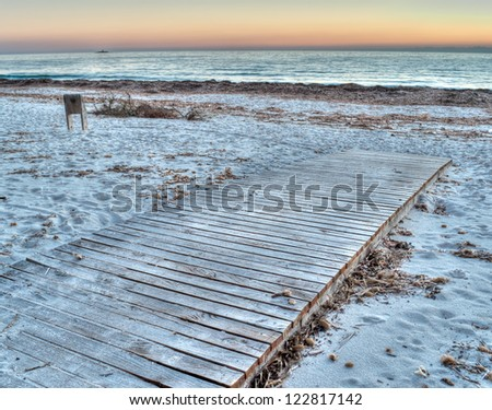 boardwalk by the sea at sunset in hdr toning - stock photo