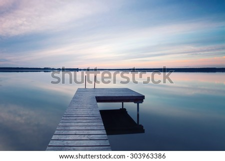 boardwalk leads out onto the lake, silent at lake while sunrise  - stock photo