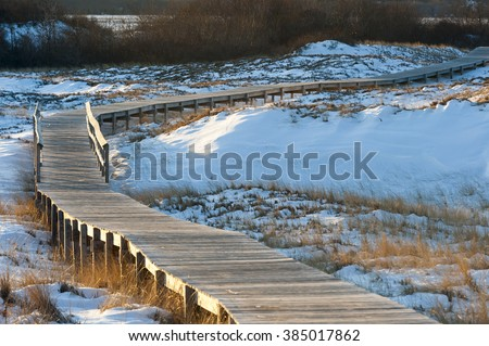 Boardwalk meanders across snow-covered sand dunes - stock photo