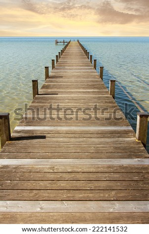boardwalk to the endless horizon and open sea. Morning mood at sunrise - stock photo