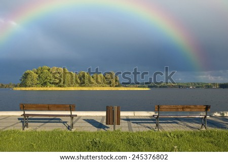 Boardwalk with empty benches on beautiful lakeshore with rainbow on the sky - stock photo