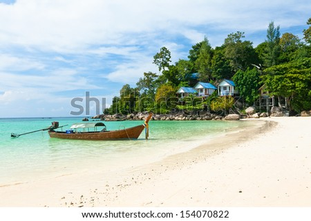 Boat and bungalows on the beach of Koh Lipe Island, Thailand. - stock photo