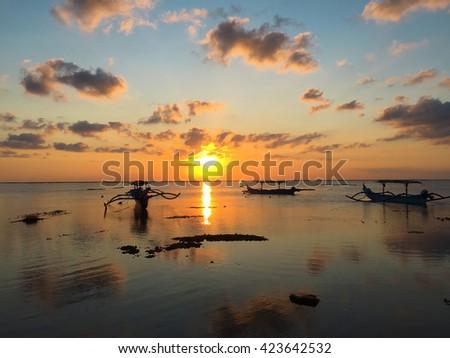 Boat and sea, sunset time in sea, fisherman boat in sunset sea, boat on sunset, sea horizon during sunset, still sea and boat, catamaran boat in sea, Bali sea on sunset, orange sunset sky and sea - stock photo