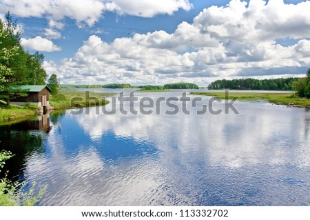 Boat and wooden house on the lake in Finland - stock photo