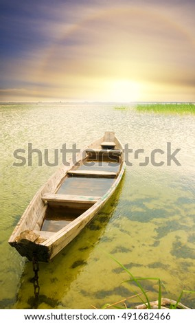 Boat at coast against asunset. Nature composition.