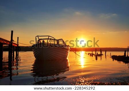Boat at sunset beach - stock photo