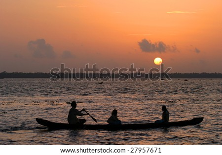 Boat at sunset with the people in kerala area - stock photo