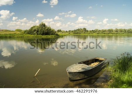 Boat beside riverside on background blue sky with white cloud