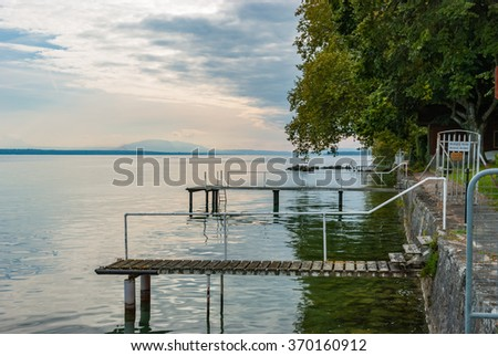 Boat bridge on Swiss Lake Leman lakeshore  Wooden jetties on a Lake Geneva shore with steps off a cement quay and overhanging green trees, no boats and a scenic view over the water - stock photo
