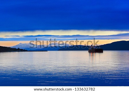 Boat (bulk carrier) on the fjords of Norway, mountain in the background with sunset light. - stock photo