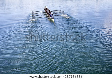 Boat coxed eight Rowers rowing on the tranquil blue lake - stock photo