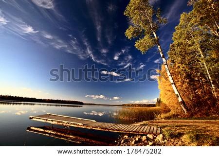 Boat dock and autumn trees along a Saskatchewan Lake - stock photo
