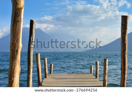 Boat dock at a small village of San Marcos on the Lake Atitlan in Guatemala with the volcanoes on the background - stock photo