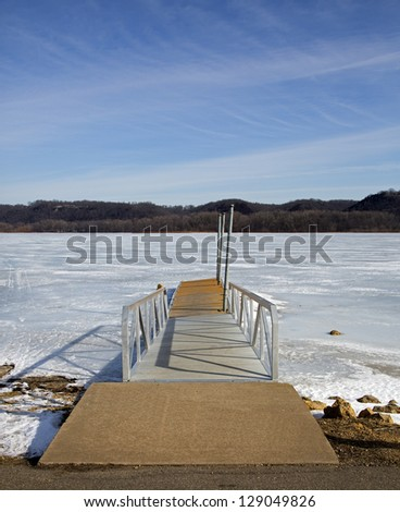 Boat dock at sunrise on a frozen lake.