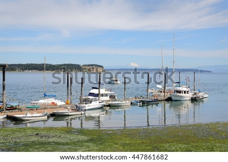 Boat Dock, Coupeville Pier, Washington State. The Boat Dock off the Coupeville Pier, Washington State, USA. Mount Baker rises in the background across Puget Sound. - stock photo