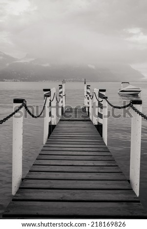 Boat dock in Menaggio, Lake Como Italy. Nautical, travel, European vacation, boating and yachting concept. Black and white. High contrast  - stock photo