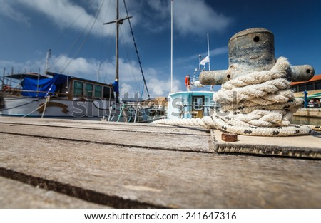 Boat docking point at a marina - rope fixed around a belay in a small harbor - stock photo