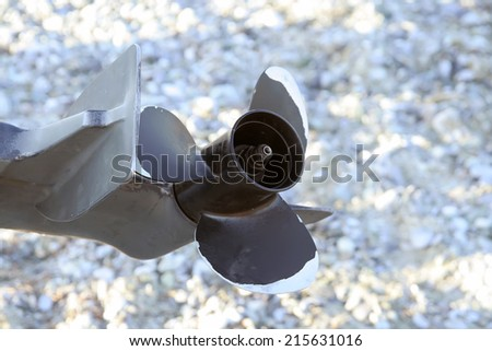 Boat engine propeller. Boat propeller on the sand beach. - stock photo