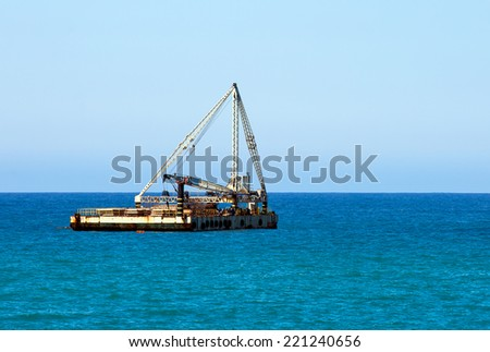 Boat equipped with heavy crane to lift cargo  - stock photo