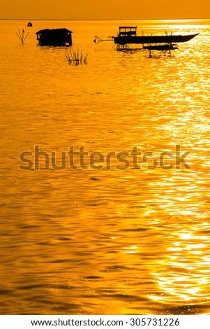 Boat freshwater lake sunset Cambodia  - stock photo