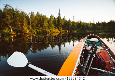 boat goes over the smooth water of the lake before sunset - stock photo