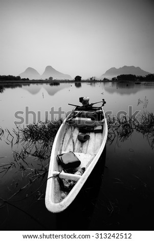 Boat in black and white with lake and hills background