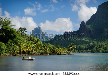 Boat in Cooks Bay with Moua Puta mountain in the background in a green jungle landscape on the tropical island of Moorea, near Tahiti in the Pacific archipelago French Polynesia.