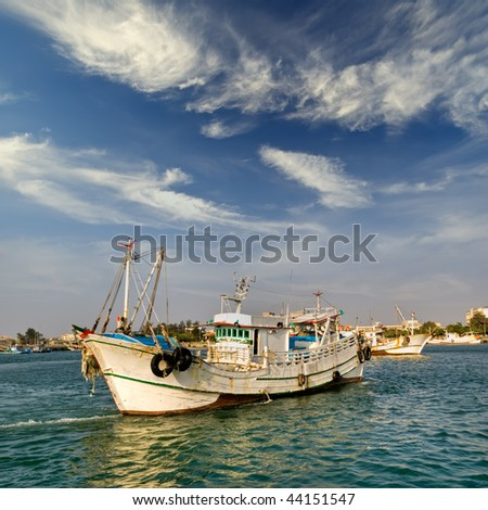 Boat in harbor with dramatic wave and sky in Tainan city, Taiwan. - stock photo