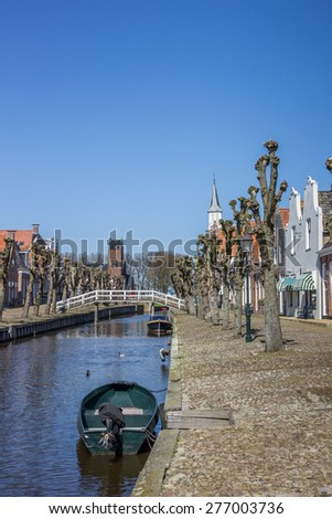Boat in the central canal of historical Sloten, Netherlands - stock photo