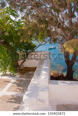 boat in the sea can be seen through the frame of trees - stock photo