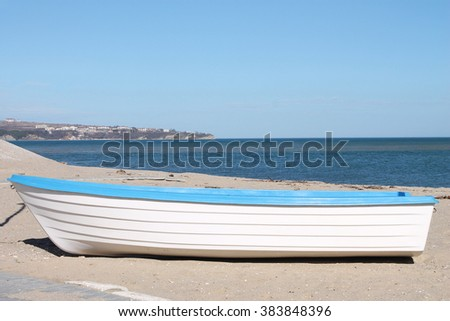 Boat in white color with a blue stripe placed on the sand on the beach - stock photo