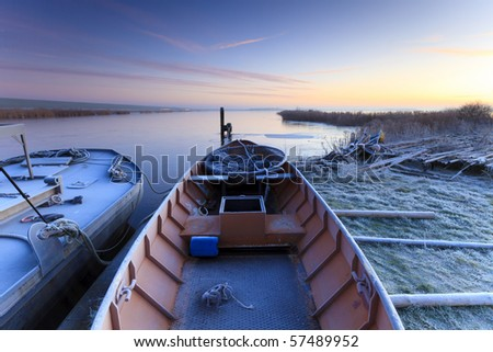Boat in winter and a beautiful sunrise - stock photo