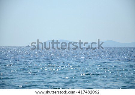 Boat is sailing across the sea in distance