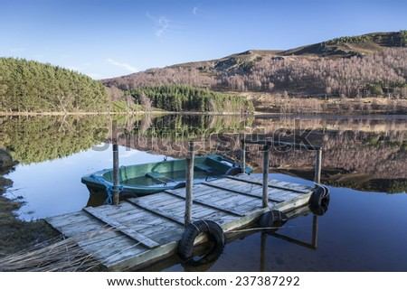 Boat & jetty on Loch Pityoulish in Scotland. - stock photo