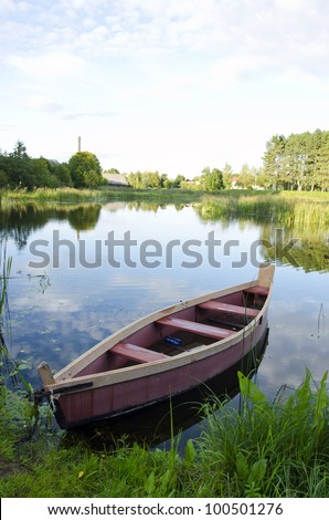 boat moored with chains at river shore. water transportation. green lake flora in summer. - stock photo