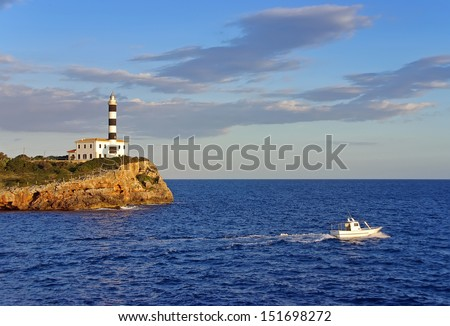 Boat navigating near an ancient lighhouse in spain - stock photo