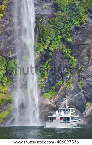Boat near spectacular waterfall, Milford Sound fiord, New Zealand - stock photo