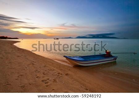 Boat near the beach at sunset - stock photo