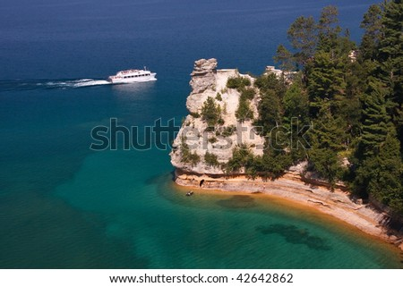 Boat next to Miners Castle on Lake Superior - stock photo
