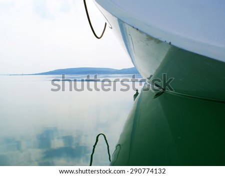 Boat on a perfectly still calm water surface - stock photo