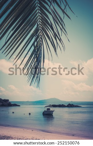 Boat on a Tropical beach at Curieuse island Seychelles. Vertical shot polaroid like - stock photo